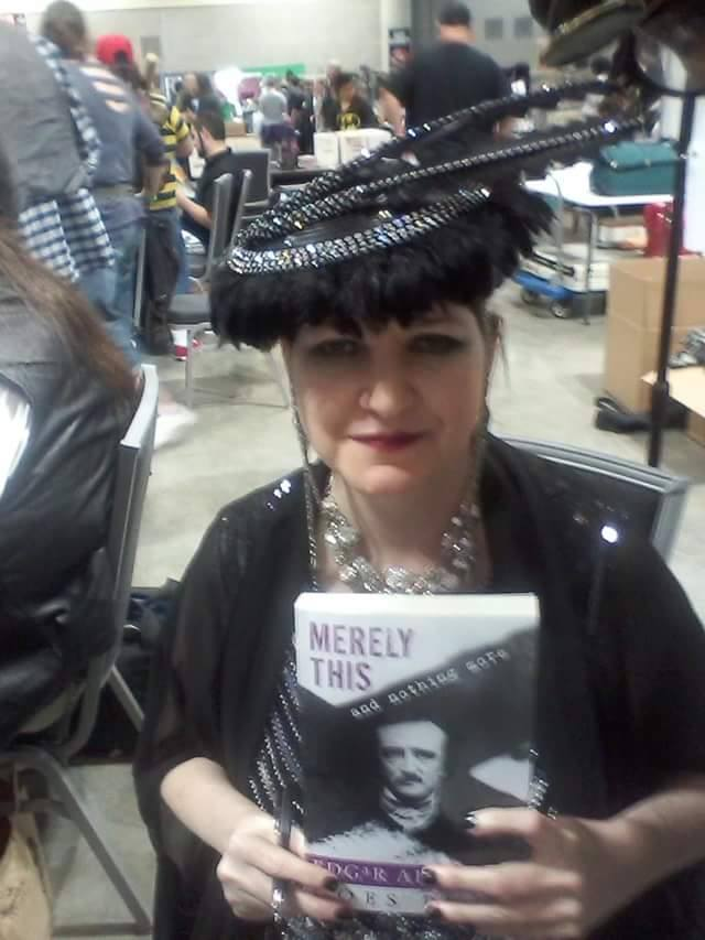 Author Holly Gonzalez in full decopunk cosplay and signing copies of Poe Goes Punk at a convention.